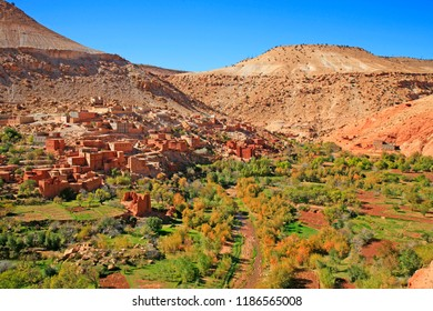 Village with mosque, red houses and little forest along the Draa river and High Atlas mountains, Morocco