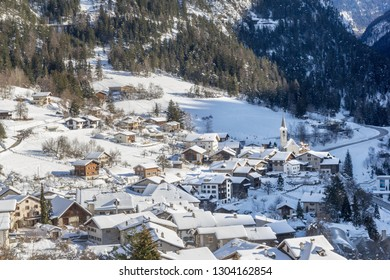 Village in a narrow valley in winter afternoon in the swiss alps.