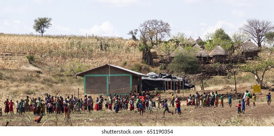VILLAGE NEAR KONSO, OMO VALLEY, ETHIOPIA - JANUARY 3, 2014: Children and teachers of rural school at a school playground do some sport activities on a break between classes.