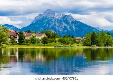 a village near the lake and the mountains on the horizon