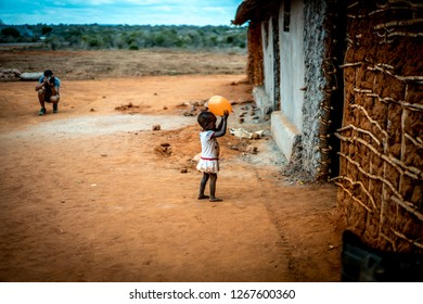 Village near Watamu, Kenya - August 2018: Poor young children and orphans with yellow school uniform playing and smiling at tourists, that give them lollipops and other charity stuffs. Black African