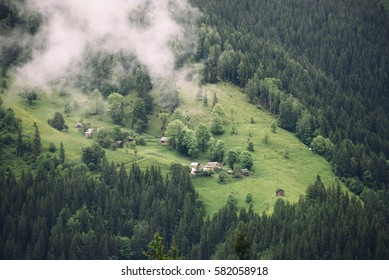 Village on a mountain hill in summer. Fog goes down.