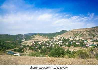 Village over mountain river. Summer day. Horizontal shot
