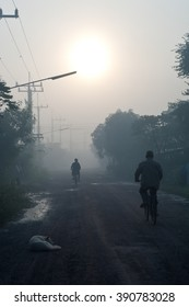 Village People riding bicycle on the country road in morning sunrise, Nakhon Ratchasima, Thailand