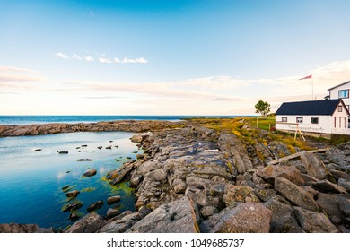 Village of Reine on Lofoten islands in Norway. Traditional wooden house. Sunset sky with clouds. Travel in Scandinavia, Europe.