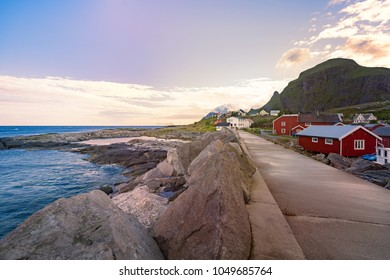 Village of Reine on Lofoten islands in Norway. Traditional red wooden houses and mountains. Sunset sky with clouds. Travel in Scandinavia, Europe.
