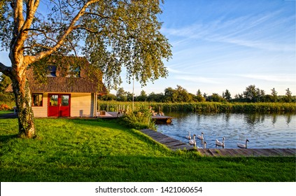 Village river house in evening. Sunset river house scene. Evening river house view. Swans at river house in evening