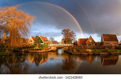 Village river houses rainbow sky landscape. Rainbow after rain over village river. Rainbow village river bridge landscape. Village river rainbow sky