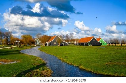Village river in summer landscape. River stream in village. Rural village river houses. Village river houses landscape