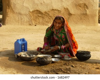 village scene in india, a young girl washing utensils