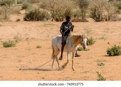 VILLAGE IN SENEGAL - APR 24, 2017: Unidentified boy in black shirt and shorts with pink stripes rides a horse in a local village in Senegal