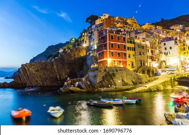 Village in a small valley at sunset, Riomaggiore, light motion blur of boats in the foreground, Cinque Terre National Park, Liguria, La Spezia, Italy