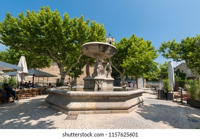 Village square with fountain and restaurant of Maussane les Alpilles. Buches du Rhone, Provence, France