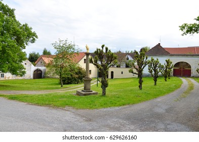 Village square with a statue in the foreground. Focus is on the statue.  /  Village square
