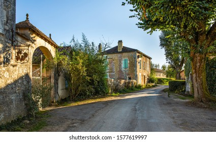 village street in France with stone houses, road and trees.