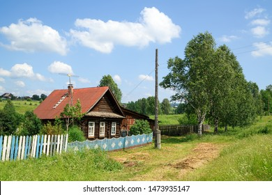 Village street in summer. Beautiful traditional log house. Village of Visim, Sverdlovsk region, Urals, Russia.