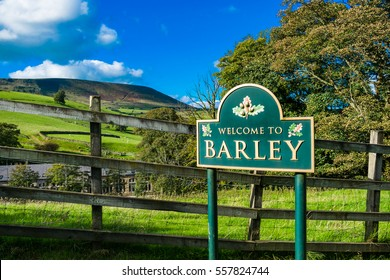 Village welcome road sign on countryside road, Pendle hill in distance, Summer, blue sky and white clouds, Forest Of Bowland, Lancashire, England, UK