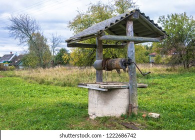 Village well under the roof with a metal chain on a cloudy autumn day, Russia.