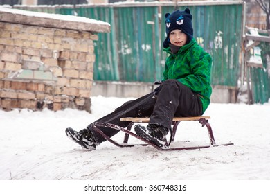 village winter: a boy in the sledge on the background of old fence