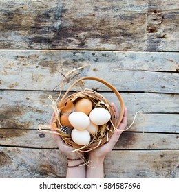 Village. Woman Holds in Hands Basket with Straw Eggs