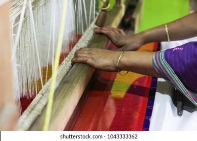 Village women busy weaving silk saree on handloom