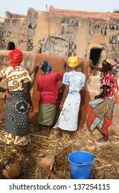 Village women paint voodoo symbols on the walls of their clay village in Benin, Africa,