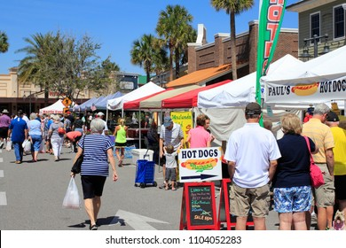 The Villages, FL, USA -April 1, 2017: Various food vendors at a farmer's market. People lined up at the street market near Paddock Square. Many people shop many farmer's market stands on a sunny day