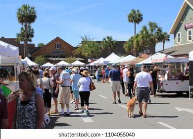 The Villages, FL, USA -April 1, 2017: People shop at a farmer's market. Street market shops under canopies sell to shoppers on a sunny day. People at farmer's market shops near Paddock Square