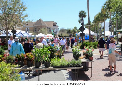 The Villages, FL, USA -April 1, 2017: People shop at an outdoor street market. People shopping at farmers market on Paddock Square streets. Farmers market shoppers buy at outdoor shops on a sunny day