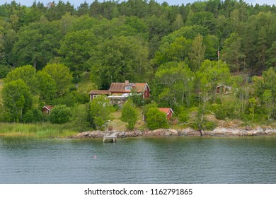 Villages on the one of the Swedish archipelagos. Summer houses surraunded with beautiful green nature, water and sky. Each have own pier. Traditional Swedish archipelago island and typical red houses