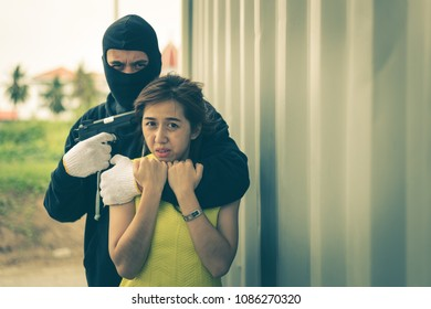The villain locks the woman's neck by his arm for a hostage and pointing gun to her head. he wear black mask and black clothes.
