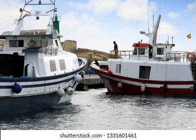 VILLAJOYOSA, SPAIN – MARCH 06, 2019. Trawler fishing boats maneuvering to be docked after a journey of fishing in the port of Villajoyosa in the Spanish Mediterranean Sea.