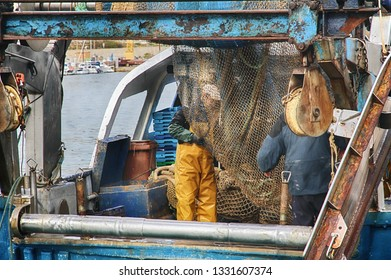 VILLAJOYOSA, SPAIN – MARCH 06, 2019. Fishermen of trawler fishing boat crew cleaning nets in the port of Villajoyosa in Spain.
