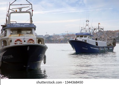 VILLAJOYOSA, SPAIN – MARCH 07, 2019. Trawler fishing boats maneuvering to be docked after a journey of fishing in the port of Villajoyosa in the Spanish Mediterranean Sea.