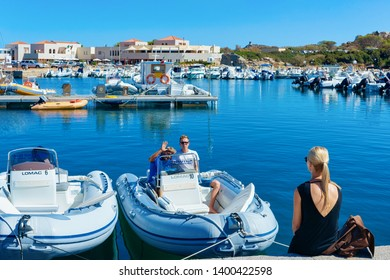 Villasimius, Italy - September 15, 2017: Lady in Old Sardinian Port with ships at Mediterranean Sea in city of Villasimius in South Sardinia Island in Italy in summer. Cityscape with Yachts and boats