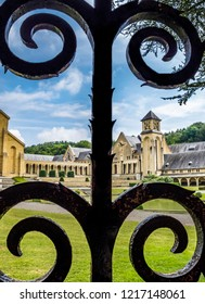 VILLERS-DEVANT-ORVAL, BELGIUM - JULY 27, 2014: The buildings of the new Trappist Cistercian Orval Abbey, Abbaye Notre-Dame dOrval behind a wrought iron fence