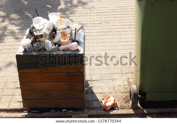 Vilnius/ Lithuania - 04 22 2019: Trash bin overfilled with plastic and paper cups on sunny day