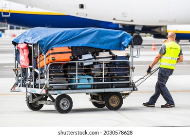 Vilnius Lithuania 2021-08-24 Worker Placing Luggage In Trailer Against Airplane
