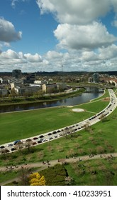 VILNIUS, LITHUANIA - APR 23, 2016: view to Vilnius on cloudy spring day in Apr 23, 2016. Neris river bank and people enjoy cherry blosom in Vilnius, capital of Lithuania. Vilnius in spring