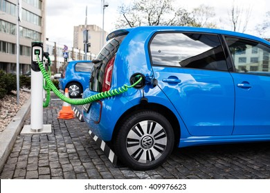 Vilnius, Lithuania - April 23, 2016: Power supply for electric car charging. Electric car charging station. Close up of the power supply plugged into an electric car being charged.