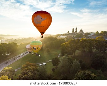 VILNIUS, LITHUANIA - AUGUST 20, 2020: Colorful hot air balloons taking off in Old town of Vilnius city on sunny summer morning. Lots of people watching as balloons fly away.