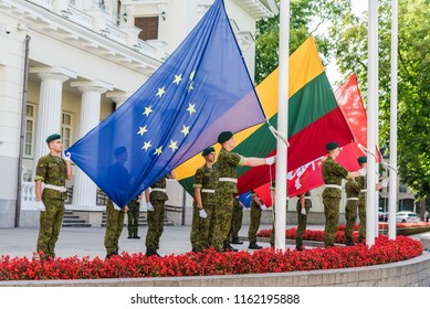 VILNIUS, LITHUANIA - AUGUST 22, 2018: Europ Union flag and Lithuanian flags rising up by Lithuanian soldiers in Daukantas square near Presidential Palace.