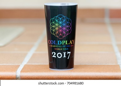 VILNIUS, LITHUANIA - AUGUST 25, 2017: The official Coldplay, a British rock band travel mug from the A Head Full Of Dreams Wold Tour 2017. One object on neutral shallow background.