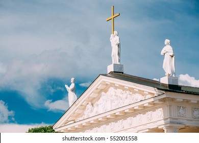 Vilnius Lithuania. Close Pediment Of Cathedral Basilica Of Sts. Stanislaus, Vladislav With Three Statues: Sts. Elena With Cross, Stanislaus, Casimir, Relief Sculpture Decoration, Blue Sky