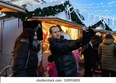 Vilnius, Lithuania - December 4, 2016: Young couple making selfie on Christmas market at Cathedral Square in the old town, Vilnius, Lithuania.