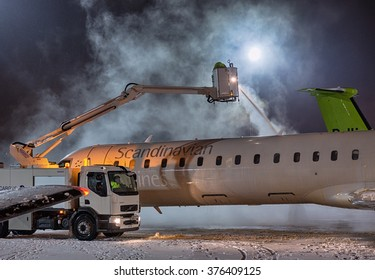 VILNIUS, LITHUANIA- FEBRUARY 12, 2016: Ground crew provides de-icing of Scandinavian Airlines CRJ-900 before take off at Vilnius airport on February 12.