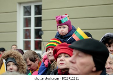 Vilnius, Lithuania - February 16, 2018:  A little girl bearing a Lithuanian flag watches a state ceremony to mark the 100th anniversary of the restoration of Lithuanian statehood.