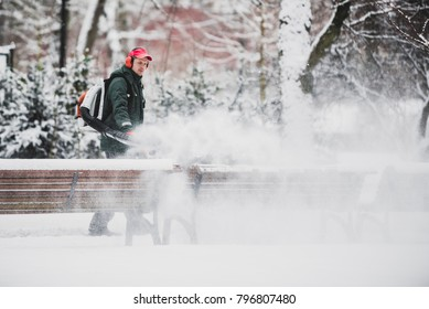 VILNIUS, LITHUANIA - January 18, 2008: Winter started. Workman cleaning snowy benches with leaf blower in the park.