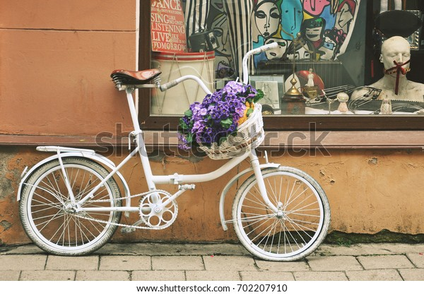 Vilnius, Lithuania - July 26, 2017: A white vintage bicycle with a basket full of blue flowers and a street in Vilnius.