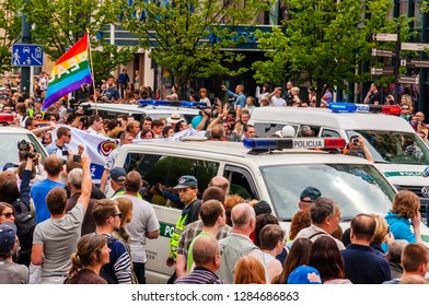 Vilnius, Lithuania - July 27, 2013: Police cars driving during the Pride parade on Gedimino street full of people. Event celebrating lesbian, gay, bisexual, transgender, LGBTI culture pride